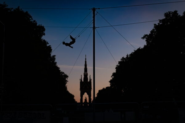 An artist from the Gorilla Circus flying Trapeze School which operates in London's Kensington Gardens for the summer is silhouetted against the Albert Memorial as the sun sets